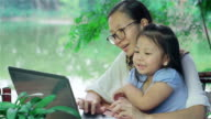 Asian Mother and Daughter using Laptop at the garden