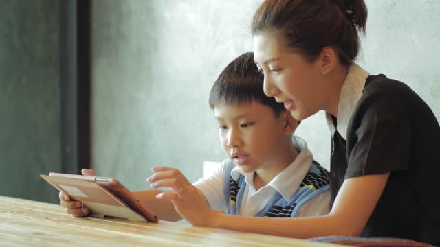 Asiatiche Madre e figlio utilizzando compressa PC