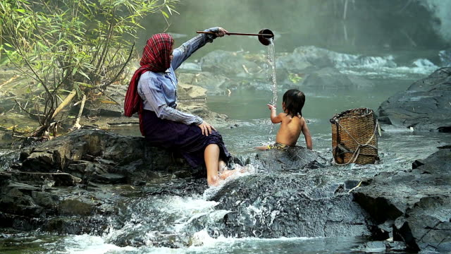 HD: Asian mother giving a kid a bath in the river