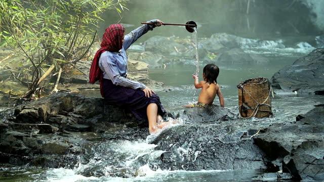 HD: Asiatische Mutter geben ein Kind ein Bad im Fluss