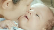 Asian mother holding and kissing the cheek of her mixed race cute little newborn baby girl in her bedroom