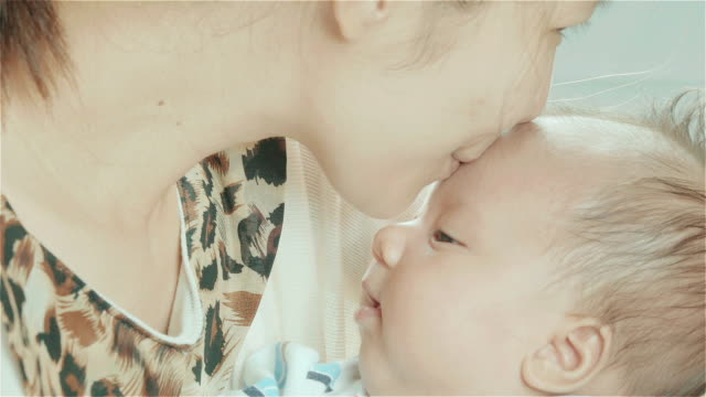 Asian mother holding and kissing the forehead of her mixed race cute little newborn baby girl in her bedroom