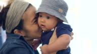 Asian mother kissing baby boy (4-6 months)