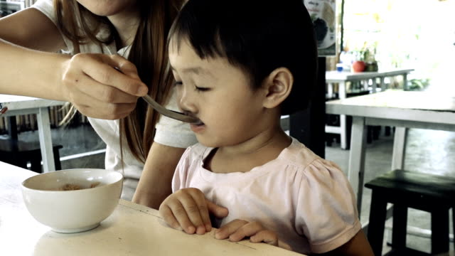 Asian mother spoon feeding her daughter