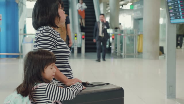 Asian mother with her daughter finding flight time at Airport