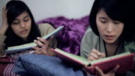 Asian multi ethnic college girls studying in bed.