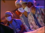 3 Asian nurses with surgical masks looking at each other while watching surgery in operating room