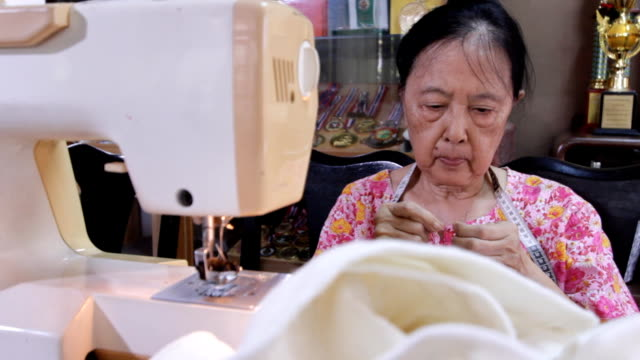 Asian old woman working with sewing machine