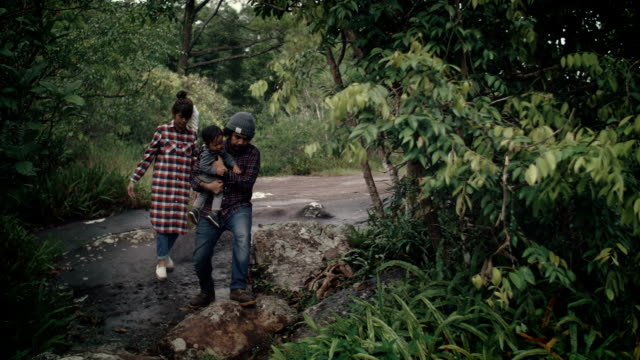 Asian parents with baby boy walking in a forest.
