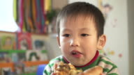 Asian preschool teacher and children eating pizza in classroom