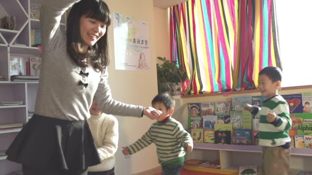 Asiatische Kinder, Lehrer spielen mit Kindern im Klassenzimmer, Zeitlupe.