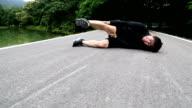 Asiatische laufenden Mann sitzt auf Straßenlage Fuß Schmerzen von Krämpfen
