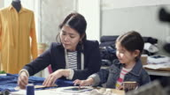 Asian seamstress with little daughter working in sewing workshop