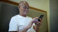 Asian senior man using moble phone indoors