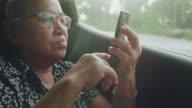 Asian senior woman using mobile phone on road trip in car