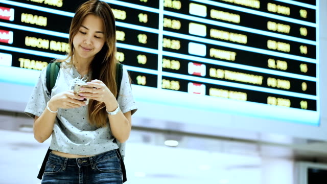 Asian tourist using phone at airport