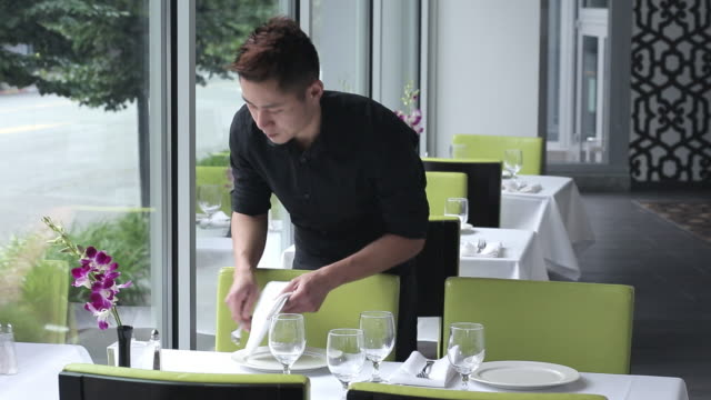 Asian Waiter Setting Table In Restaurant Stock Footage