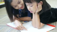 Asian woman and girl reading book in library