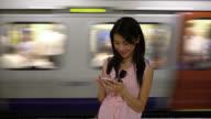 Asian woman at the subway station looking at smartphone