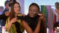 MS Asian woman + Black woman applying makeup + preparing for fashion show with male hairdresser