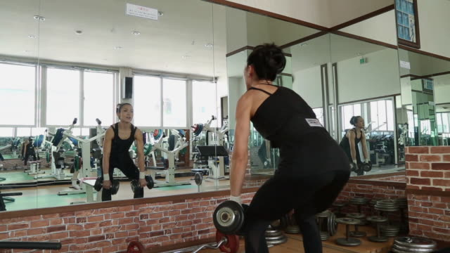 A asian woman body builder doing bent-over row dumbbell at the gym