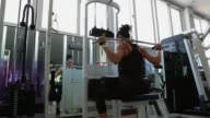 A asian woman body builder doing Lat Pull Down Machine at the gym