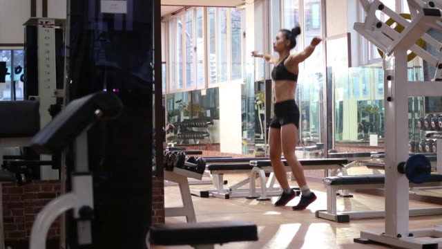 A asian woman body builder doing stretching at the gym