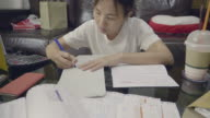 Asian Woman Calculating In Home