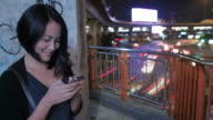 Asian woman enjoy using smartphone at Bankok city night scene with fast city moving background