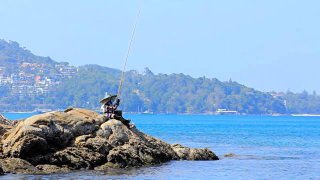 Asiatische Frau fischen auf dem rock