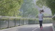 Asian Woman jogging in urban setting