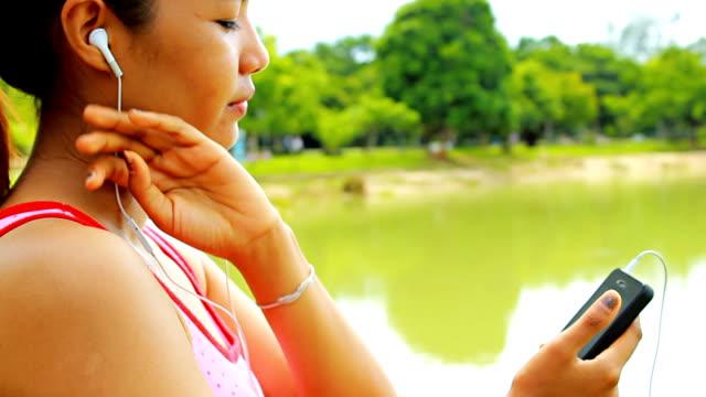 Asian Woman listen music in nature