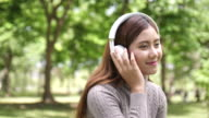 SLO MO Asian Woman listening to music on headphones