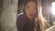 Aziatische vrouw kijken camera onder brug.