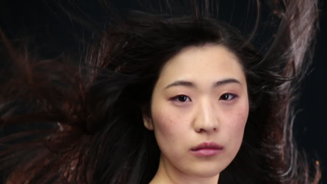CU SLO MO Asian woman looking towards moves head down and hair moving in wind / London, Greater London, United Kingdom