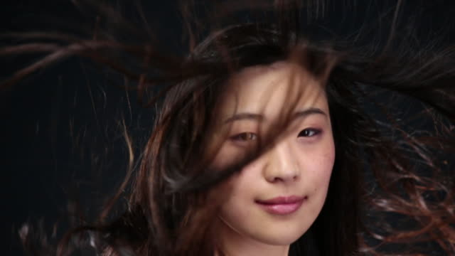 CU SLO MO Asian woman looking towards, smiling and hair moving in wind / London, Greater London, United Kingdom