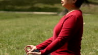 Asian Woman Meditating and Looking at Camera