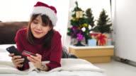 Asiatische Frau online einkaufen mit ihrem Handy auf Weihnachts-Event