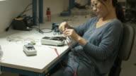 Asian woman putting away Electronic Test Equipment