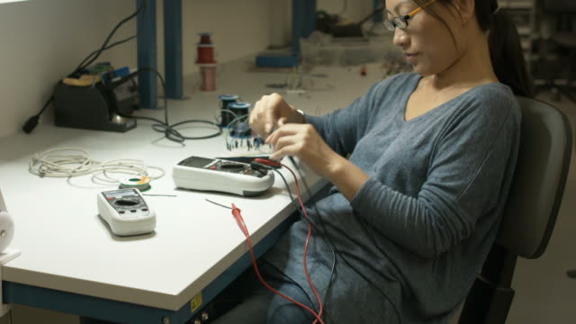 Asian woman putting away Electronic Test Equipment