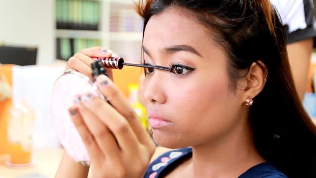 Asian Woman putting on mascara, closeup
