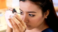 Asian Woman putting on mascara, closeup
