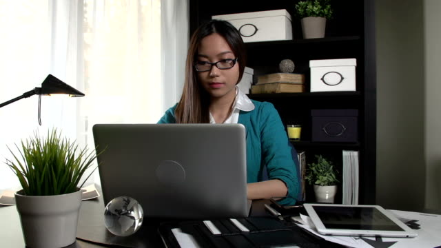 Asian woman reading a laptop computer in home office
