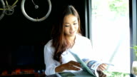 Asian woman reading magazine at coffee shop