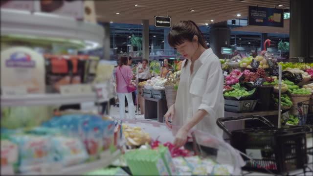 Aziatische vrouw winkelen In de supermarkt