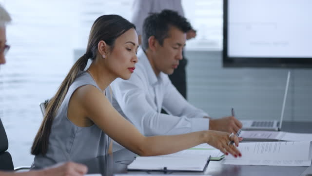 Asian woman sitting in conference room listening to female colleague giving a presentation