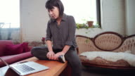 Asian woman sitting on coffee table video chatting with laptop