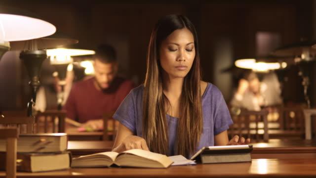 Aziatische vrouw DS studeren in de bibliotheek bij nacht