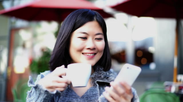 Asian woman text message, cafe.