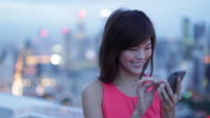 MS Asian woman texting using smartphone with citylights in background